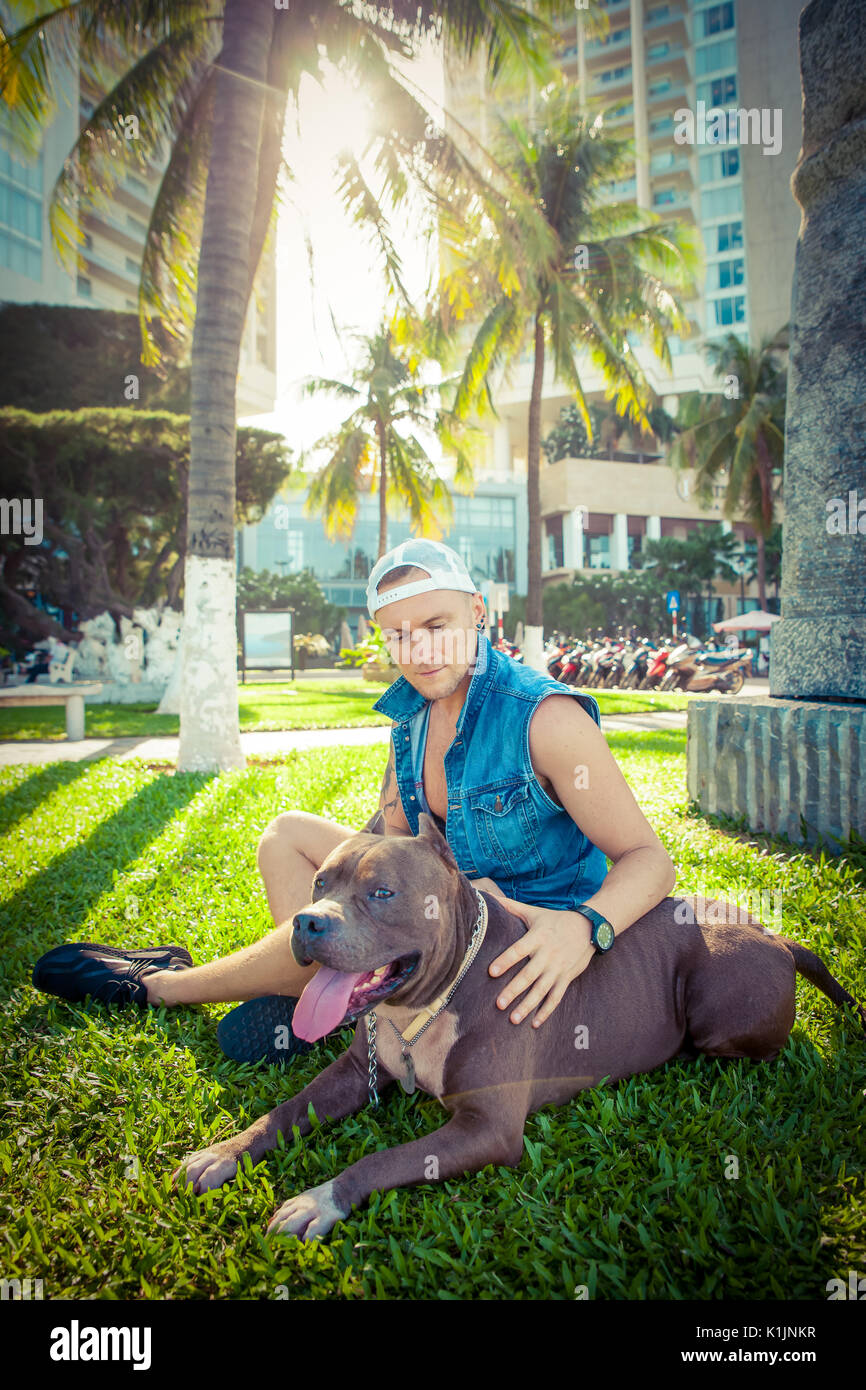 Man and dog american pit bull terrier relaxing at the park embracing and hugging - Stock Image