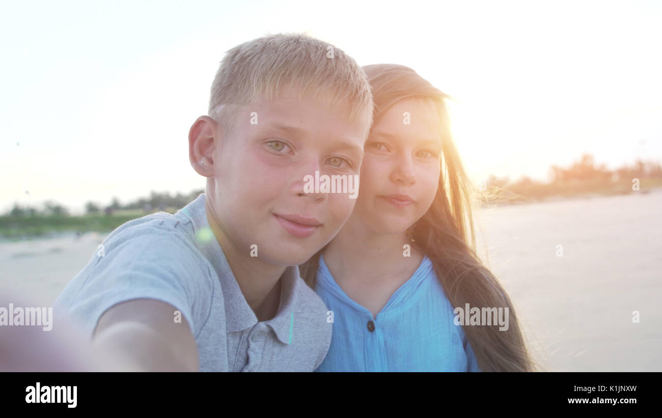 Little boy and girl of 8 - 10 years old making selfie using smartphone. - Stock Image