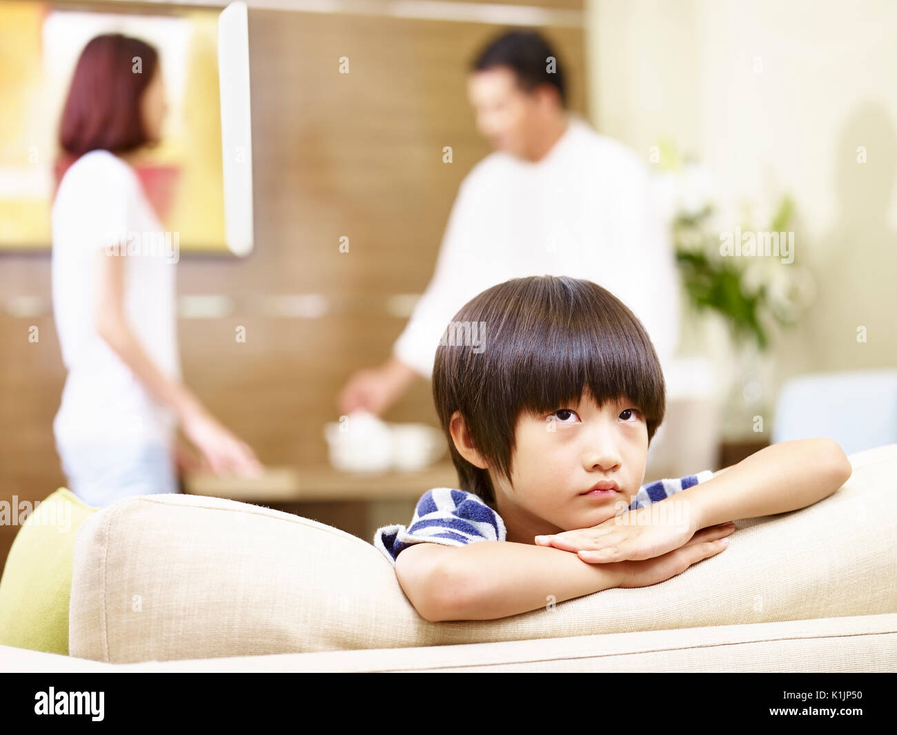 asian child appears sad and unhappy while parents quarreling in the background. - Stock Image