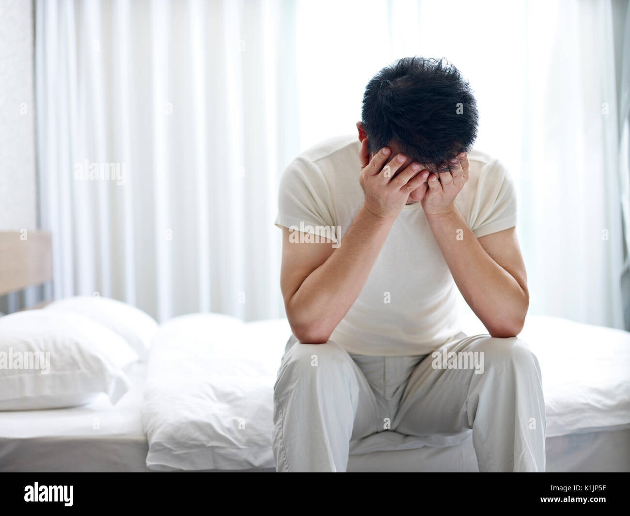 asian man suffering from insomnia sitting on bed head down covering face with hands. - Stock Image