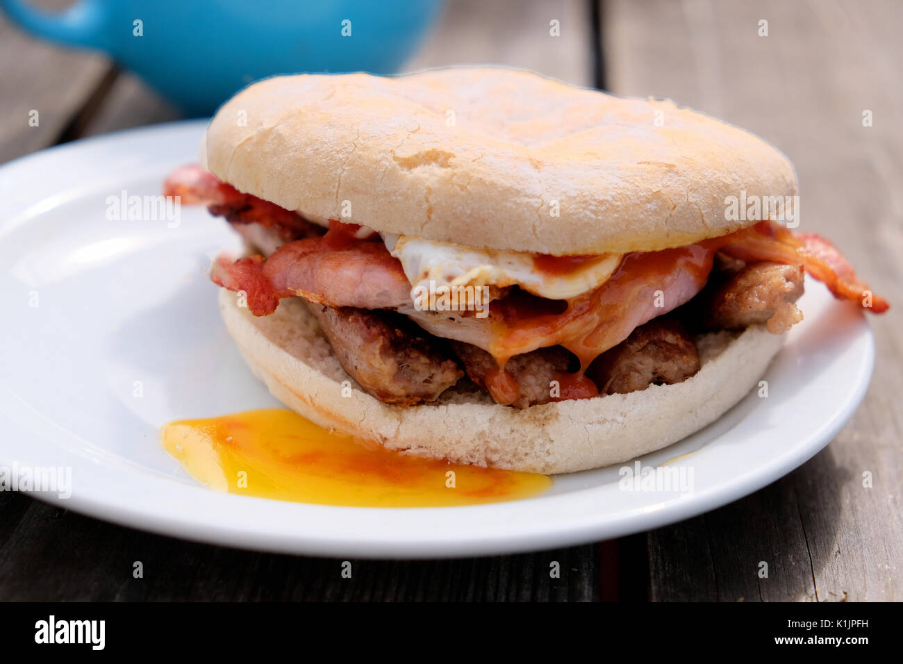 A freshly cooked breakfast bap. Bacon, sausage and fried egg cooked at a outdoor cafe and served in a bread roll. - Stock Image