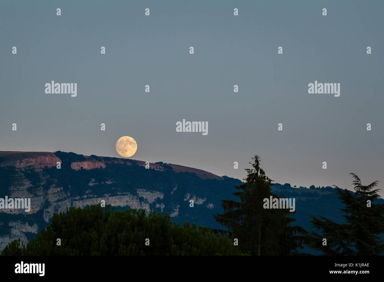 Full moon rising over the french alps. - Stock Image