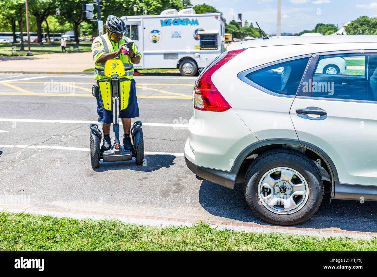 Washington DC, USA - July 3, 2017: Police traffic officer writing ticket for car illegally parked while riding segway on national mall - Stock Image