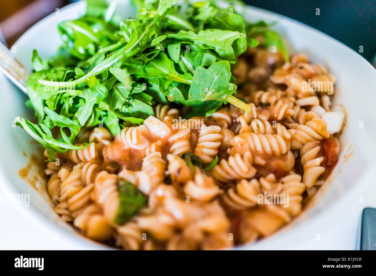 Closeup of brown rice fusilli pasta bowl in marinara sauce with arugula greens Stock Photo