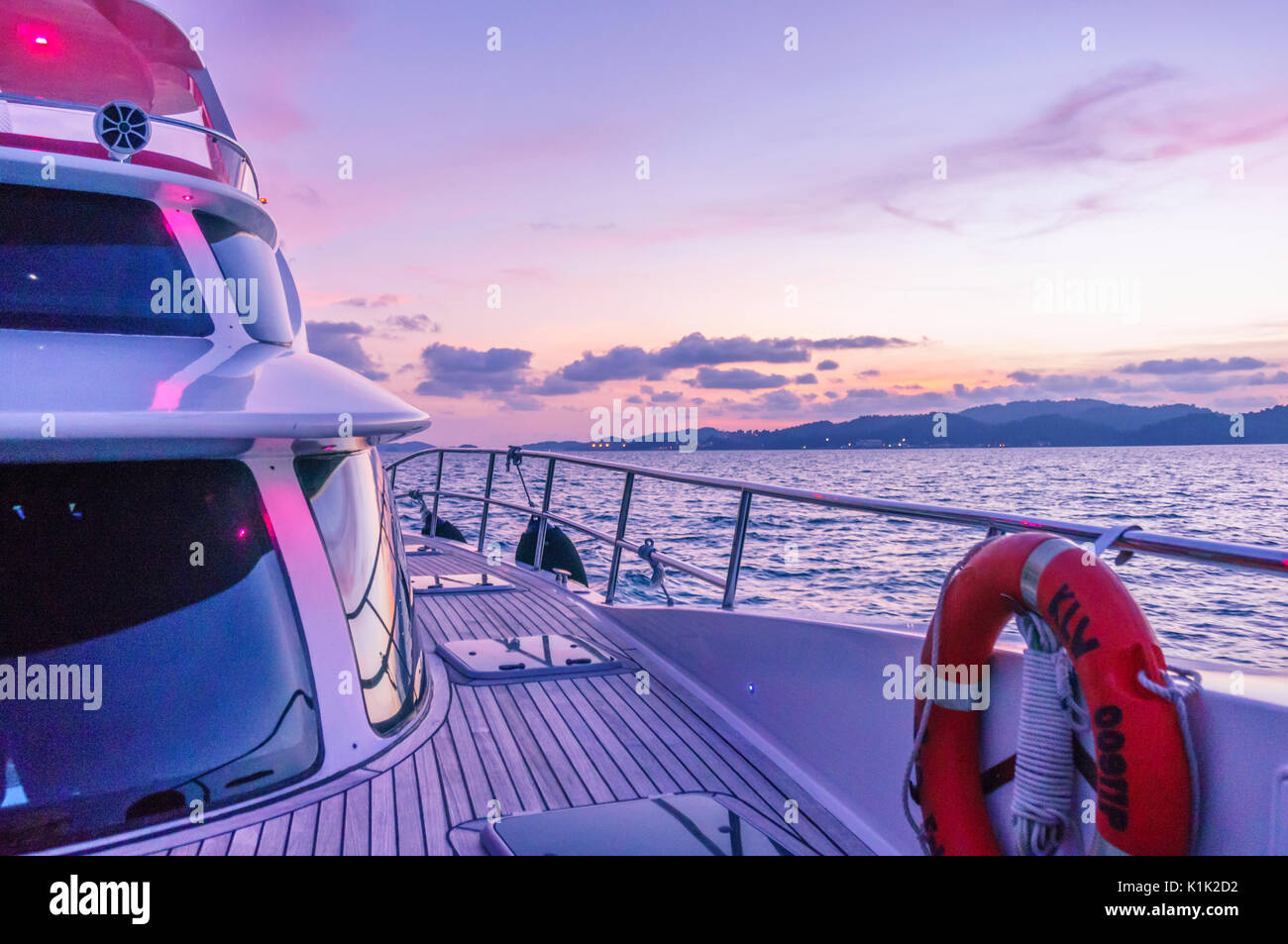 Deck of a ship shot during the purple light of dusk. The wooden deck, beautiful curved glass and modern shape show the luxury and beauty of these modern ships - Stock Image