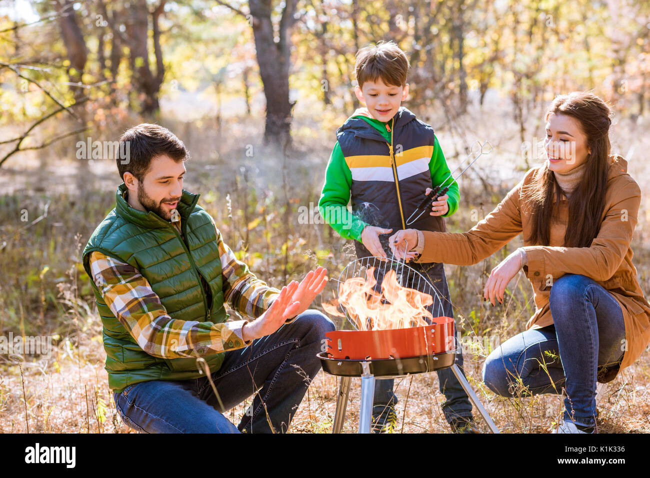 Portrait of happy family with one child preparing barbecue on grill in autumn park Stock Photo