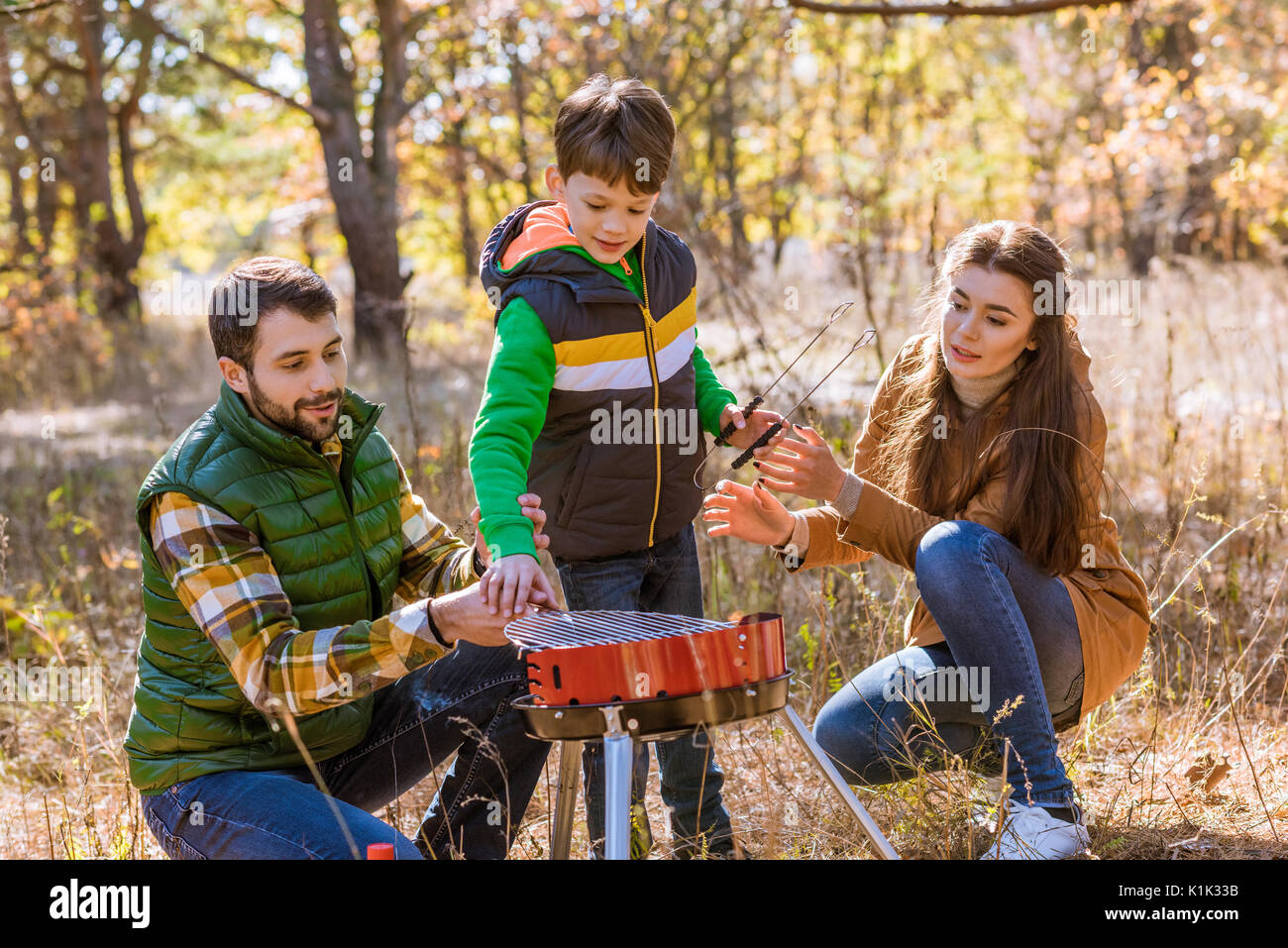 Portrait of happy family with one child preparing barbecue on grill in autumn park - Stock Image