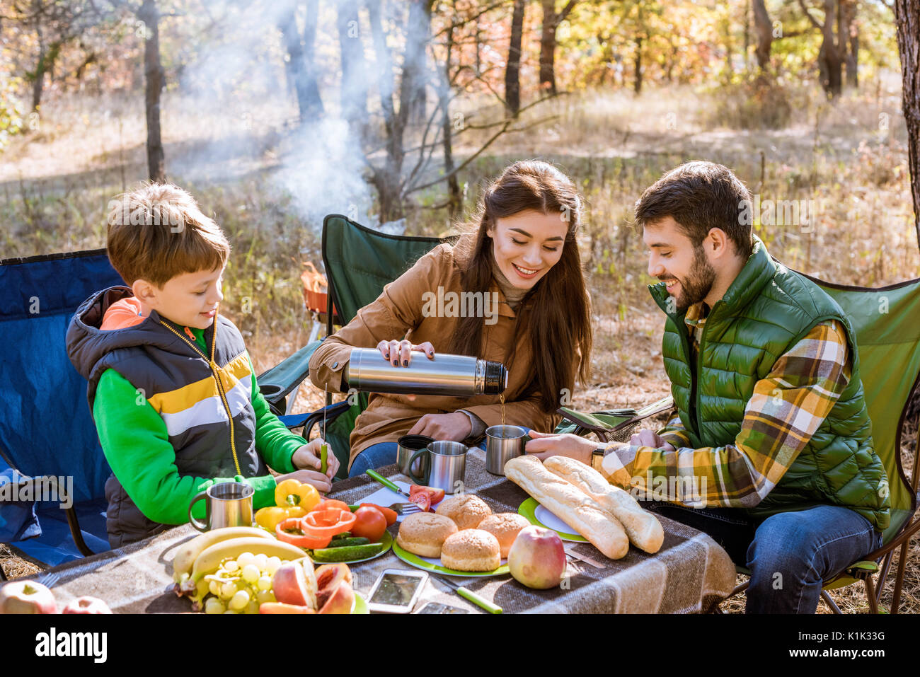 Happy smiling family drinking tea while sitting at table on picnic in autumn forest - Stock Image
