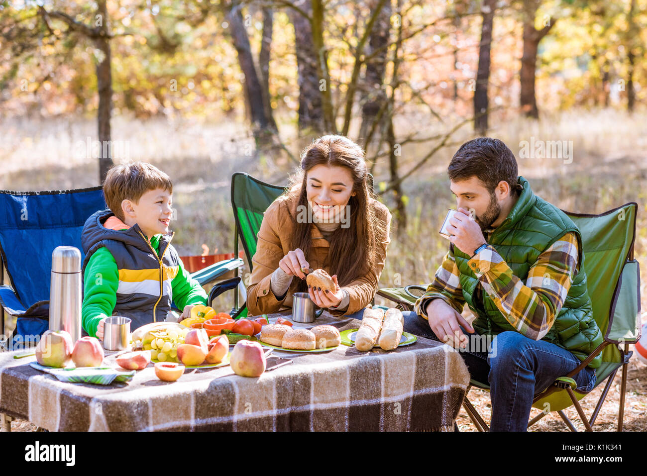 Happy smiling family eating and having fun while sitting at table on picnic in autumn forest - Stock Image