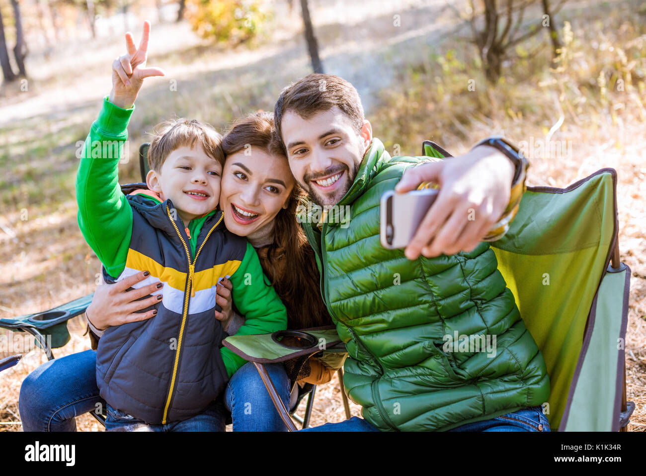 Happy smiling family at picnic having fun and taking selfie in autumn park - Stock Image