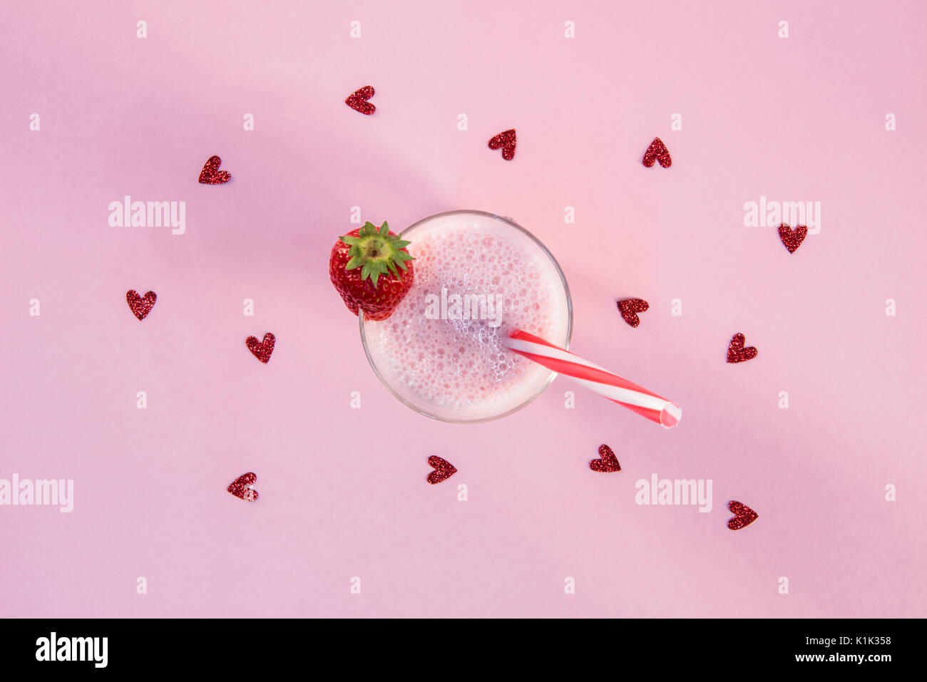 strawberry milkshake in glass with drinking straw and heart symbols on pink surface - Stock Image