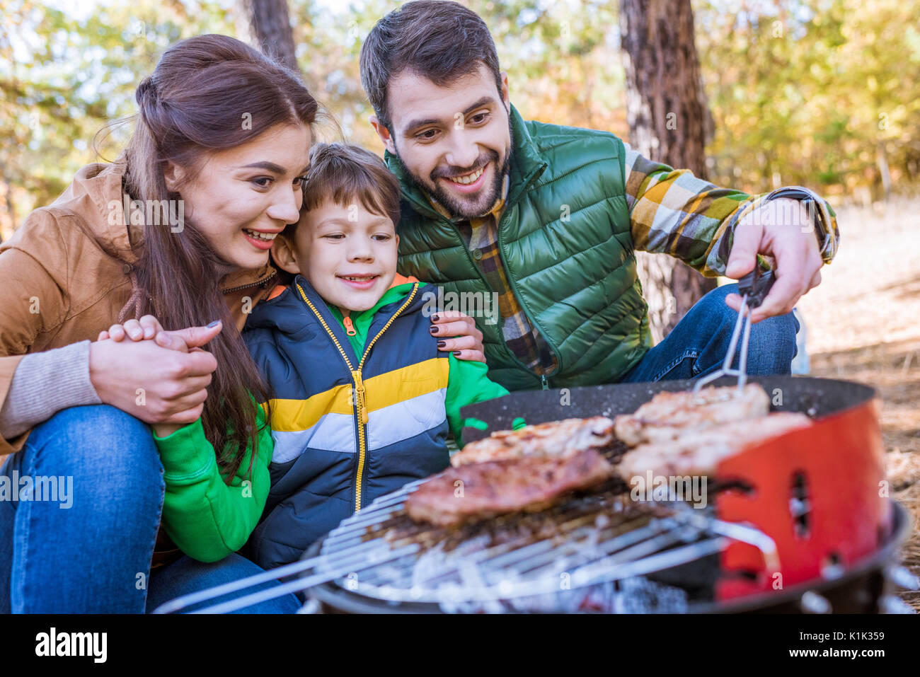Close-up portrait of happy family grilling meat on barbecue grill in autumn park - Stock Image