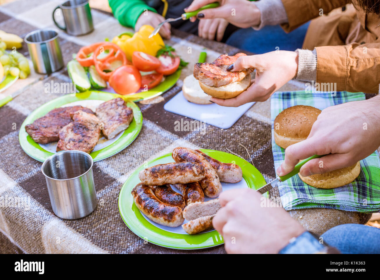 Close-up view of human hands and tasty food on table, family eating at picnic - Stock Image