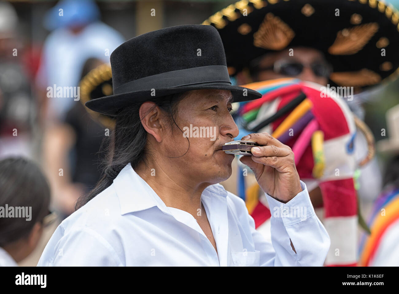 man playing the harmonica at Inti Raymi parade - Stock Image