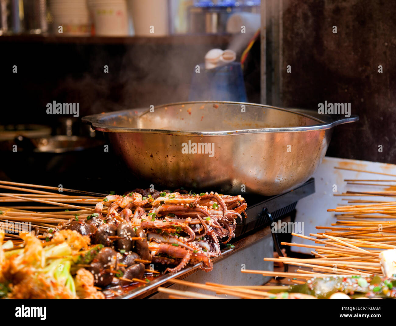 Numerous bits of skewered food, including squid, bugs, tofu, and mystery meat await the steaming wok in this tiny food stall in Ciqikou Old Town, Chon - Stock Image