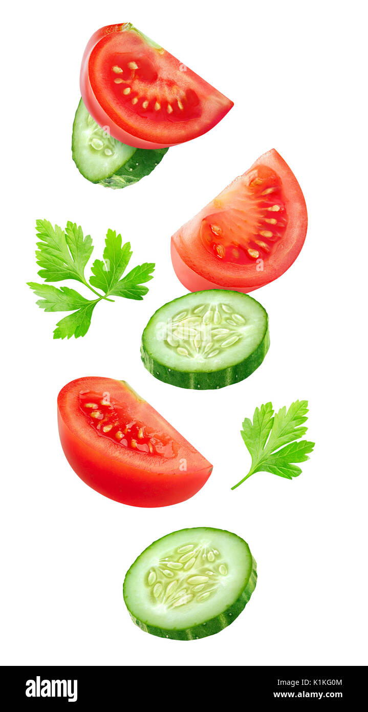 Isolated vegetables. Mixed slices of cucumber and tomato in the air isolated on white with clipping path - Stock Image