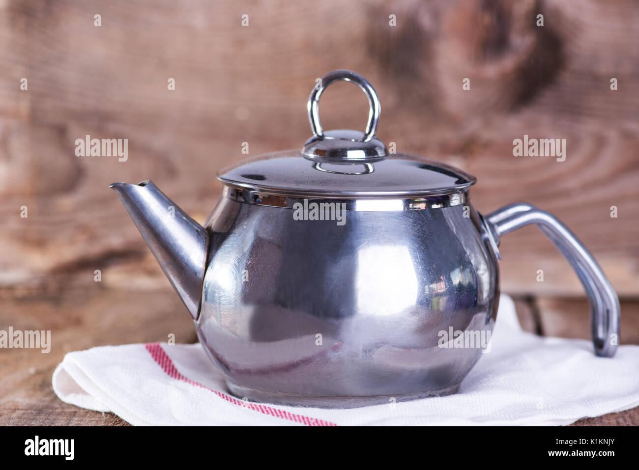 Metal tea pot on wooden background Stock Photo