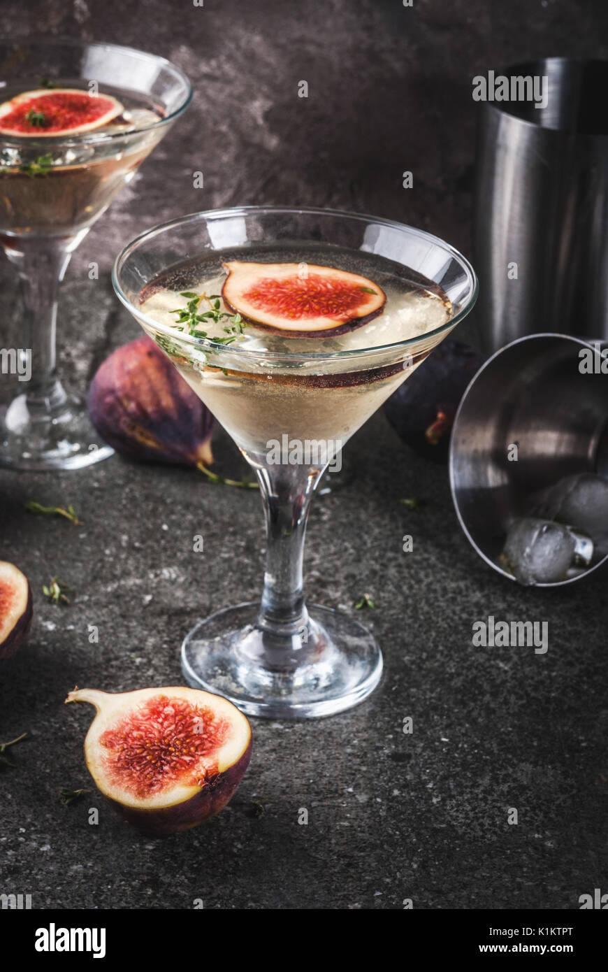 Fall and winter drinks recipes, Martini cocktail with fig, thyme and honey, on black stone table, copy space Stock Photo