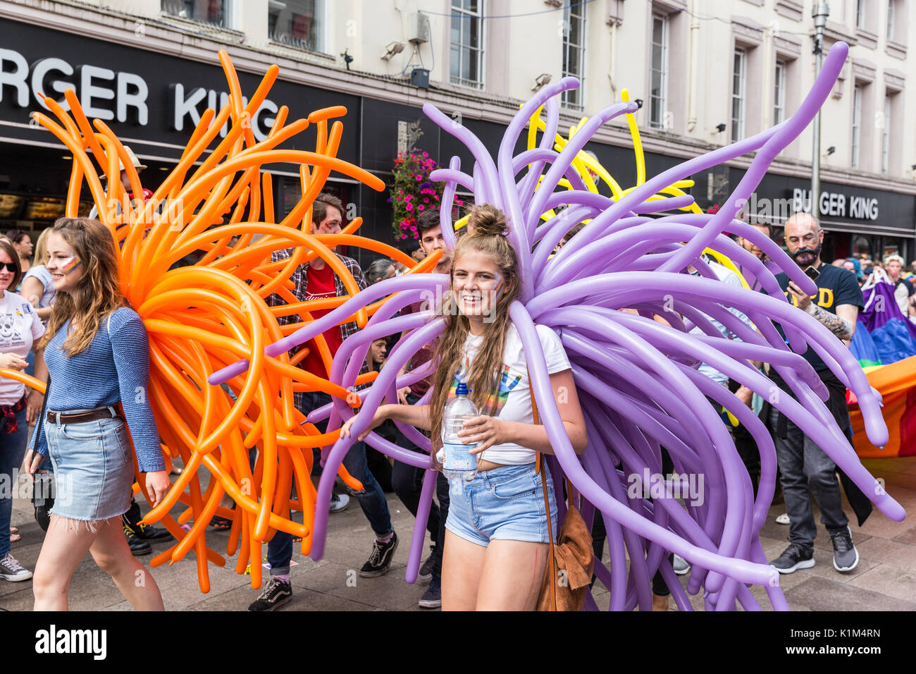 Two girls with large balloon displays march in the Cardiff Pride Parade, 2017 - Stock Image