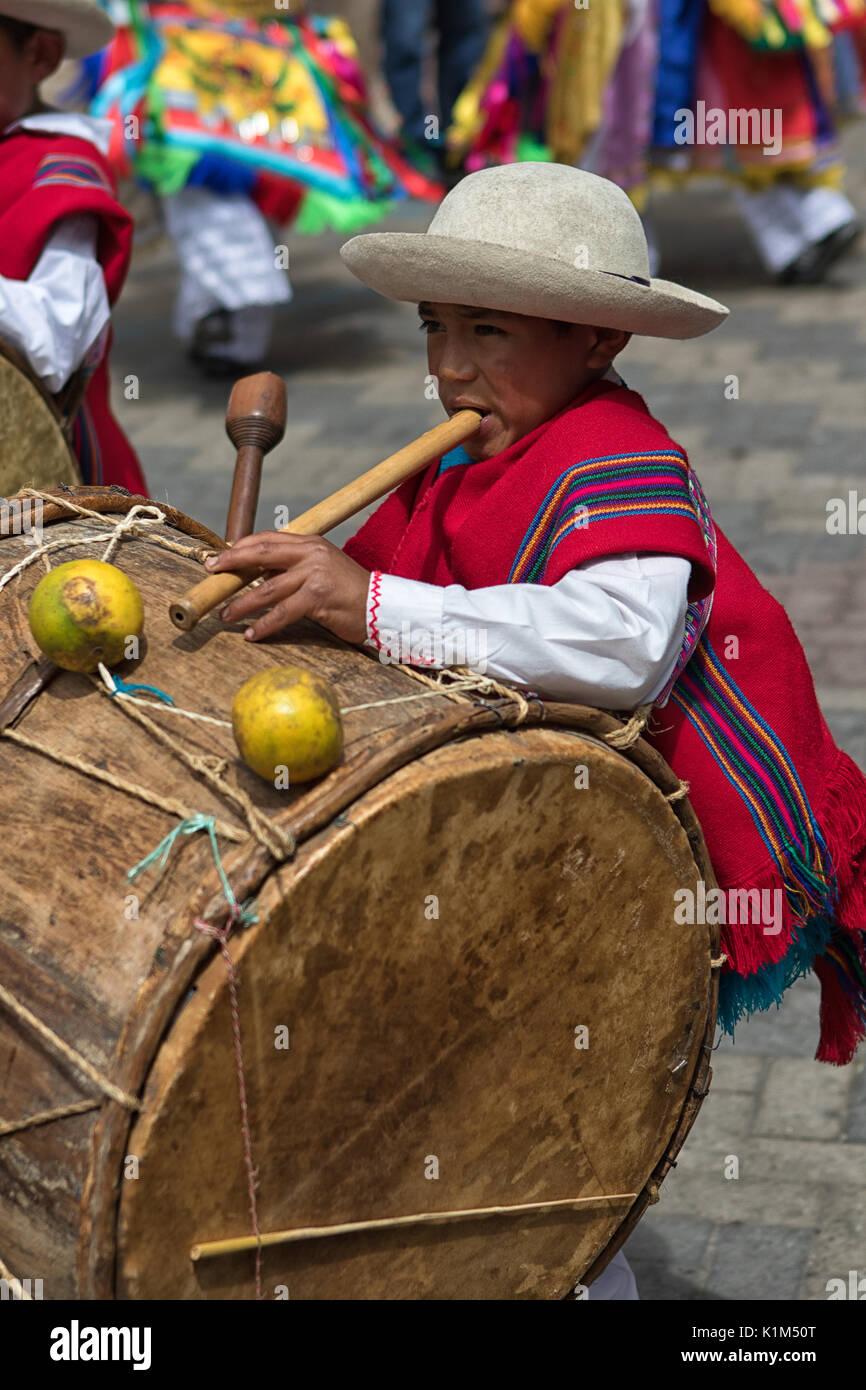 June 18, 2017 Pujili, Ecuador: young indigenous kichwa boy playing flute and drum simultaneously at parade - Stock Image