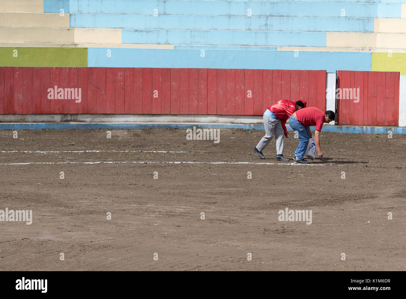 June 18, 2017, Pujili, Ecuador: men preparing the bullfighting ring before the event by marking circles on the ground - Stock Image