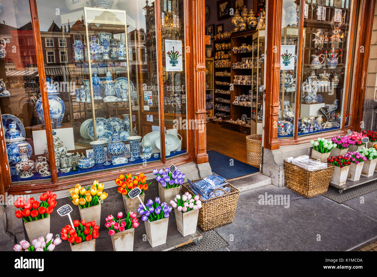 Netherlands, South Holland, Delft, blue Delftware pottery and tulips at a souvenir shop - Stock Image