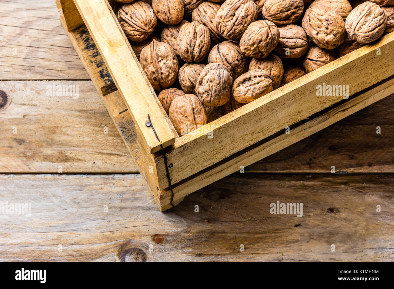 Box of walnuts on wooden background. Harvest concept - Stock Image