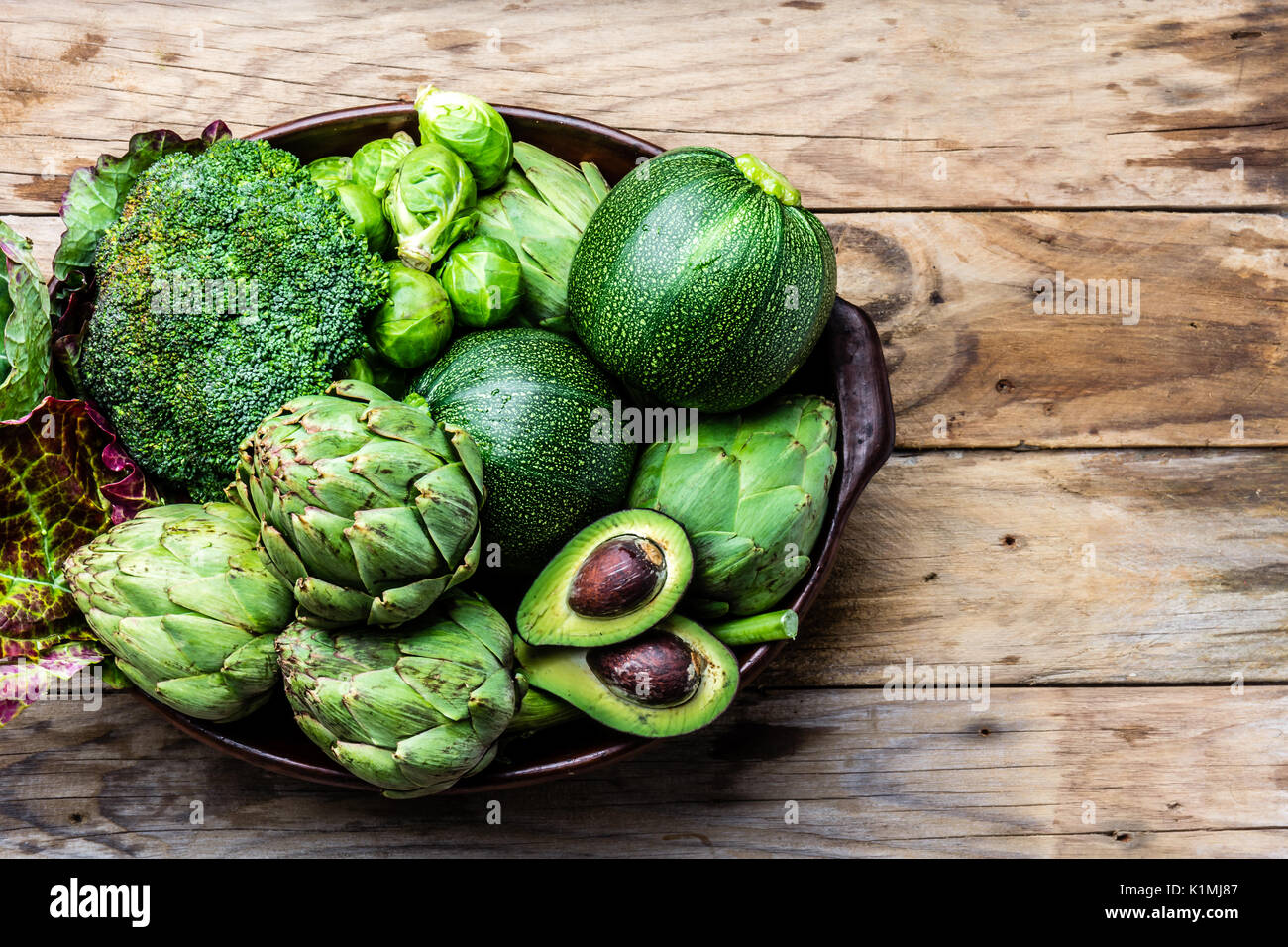 Cooking background harvest concept. Fresh organic green vegetables in clay pot on wooden background - Stock Image