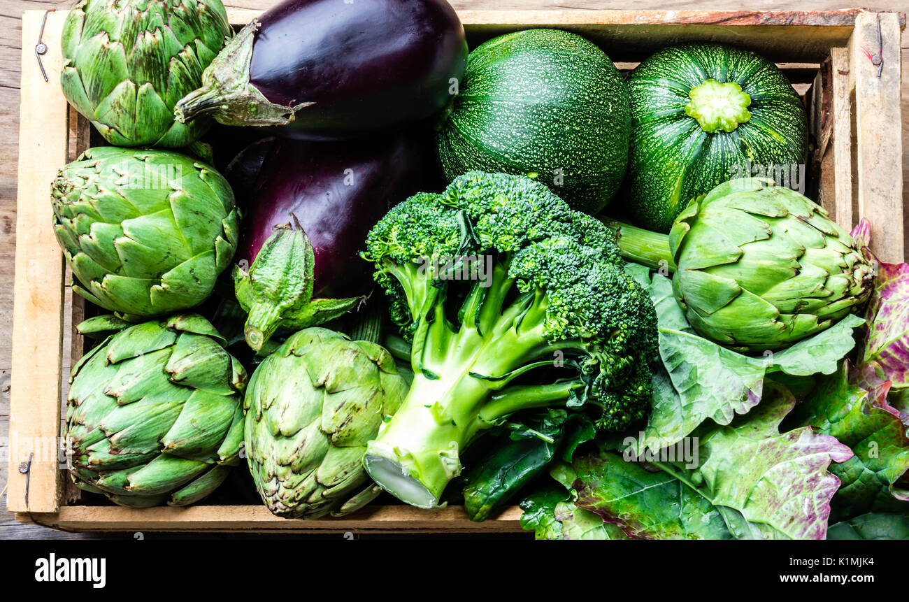 Cooking background harvest concept. Fresh organic green vegetables in box on wooden background - Stock Image