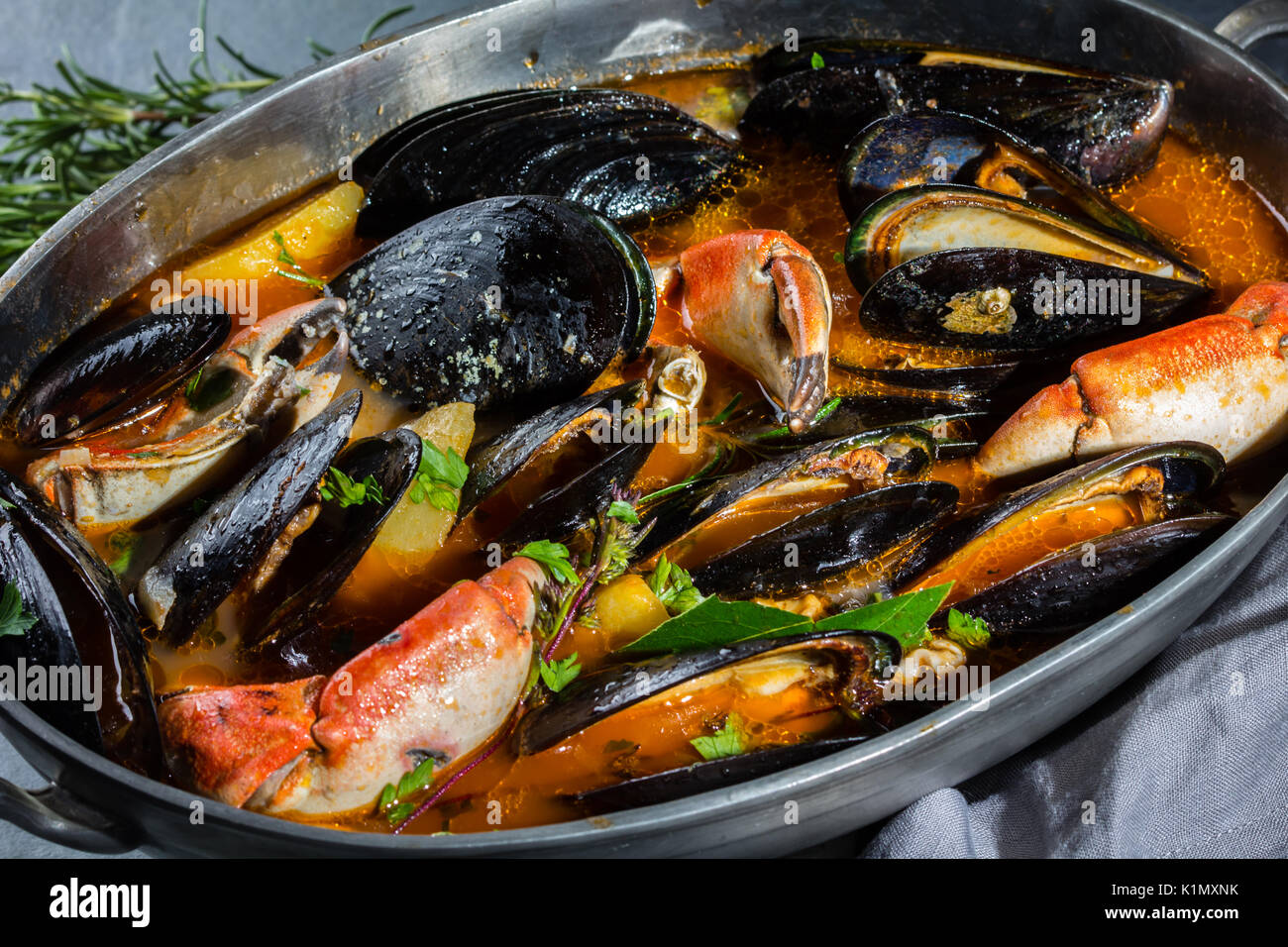 Seafood mussels crabs soup in metal pot, gray background - Stock Image