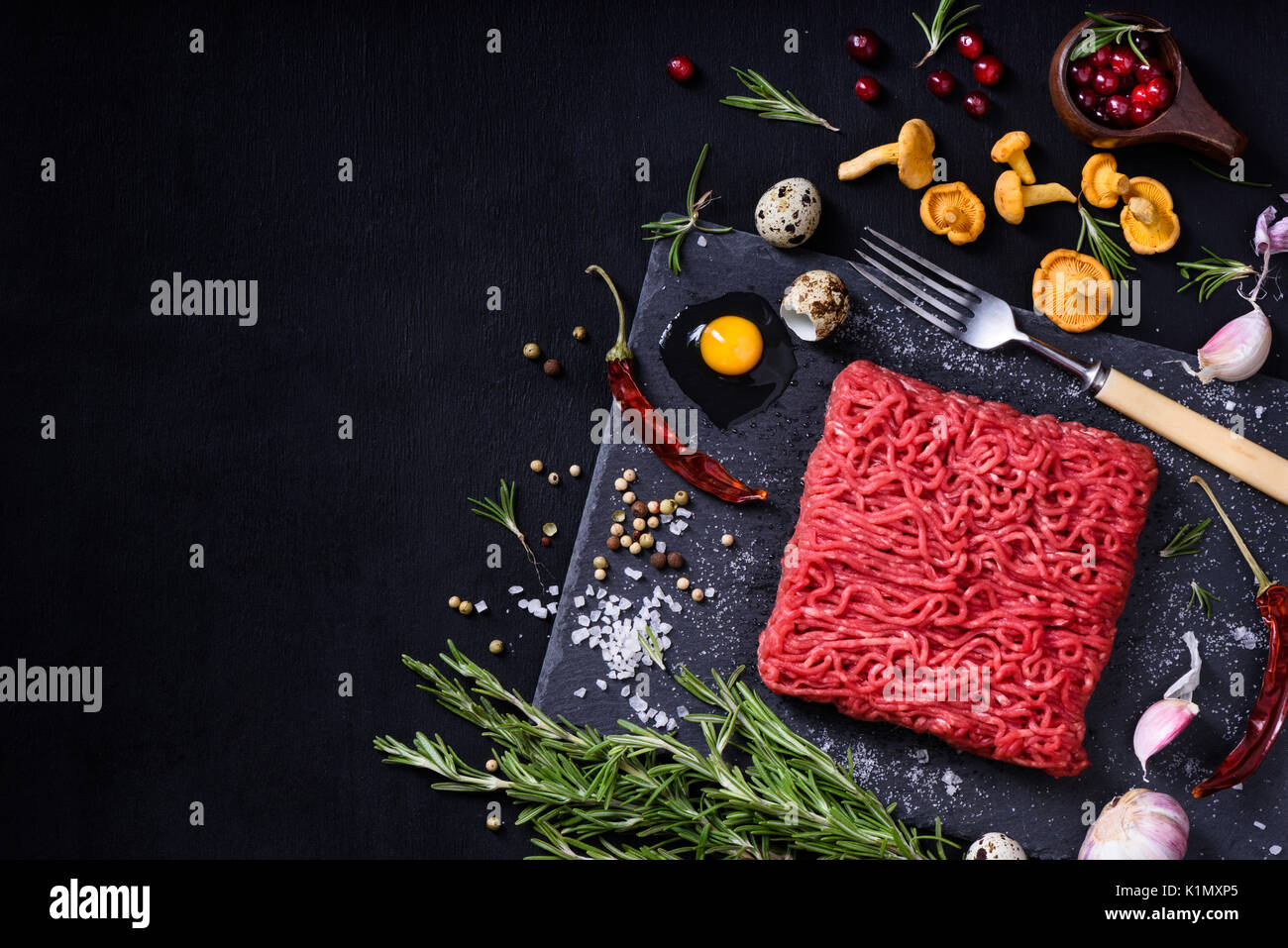 Tasty raw veal or beef meat on black table. Cooking ingredients with ground meat. Top view, copy space. Stock Photo