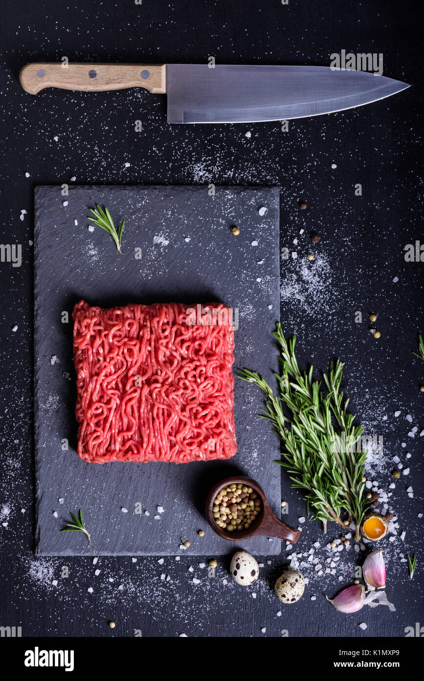 Red raw beef, with cooking ingredients, served on a stone board, kitchen knife. Top view, copy space. Stock Photo
