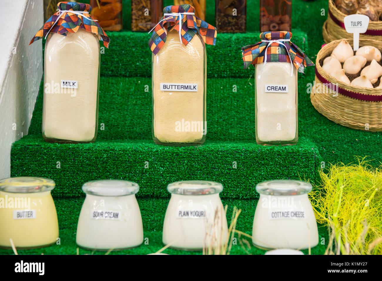 Labeled Bottles and Jars of Various Dairy Products Displayed - Stock Image