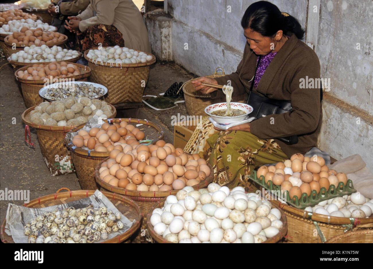 Vendor eating noodles and selling eggs at open-air market, Kengtung (Kyaingtong), Burma (Myanmar) - Stock Image