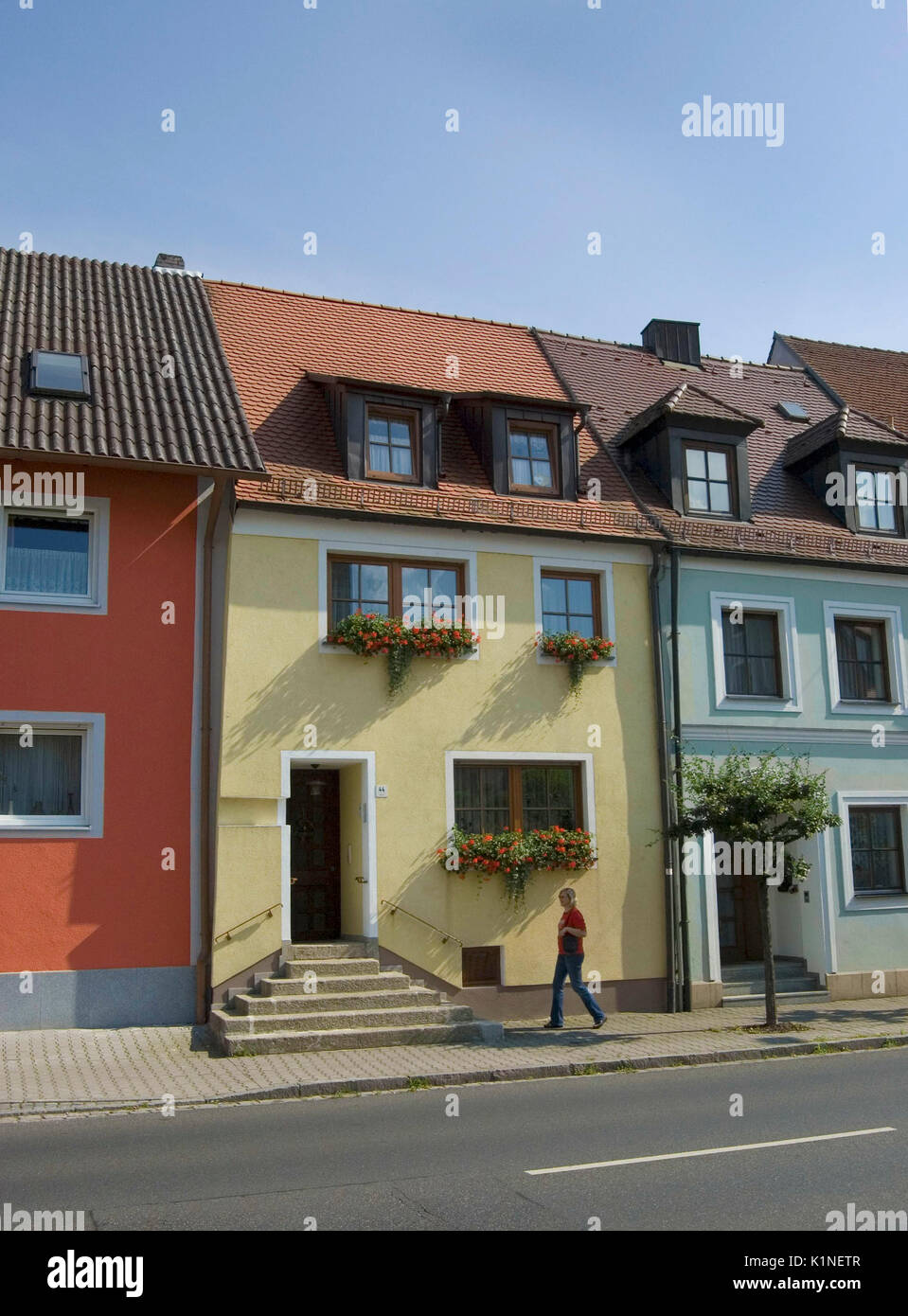 Bavaria, Germany - July 3, 2009: A woman walks past brightly painted houses with window boxes containing colorful flowers. - Stock Image
