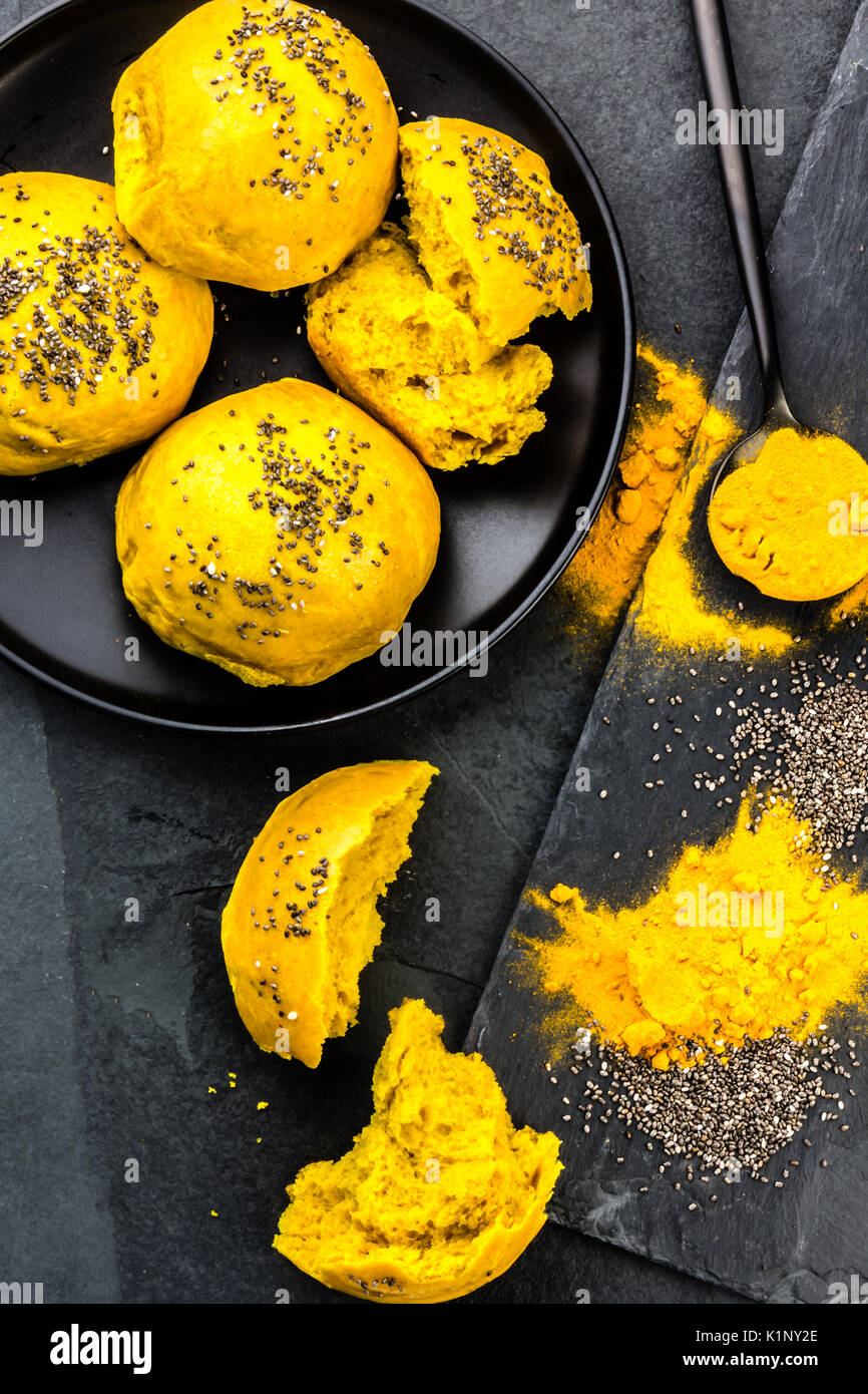 Bread burger buns with superfoods curcuma and chia on slate blackbackground. Top view - Stock Image