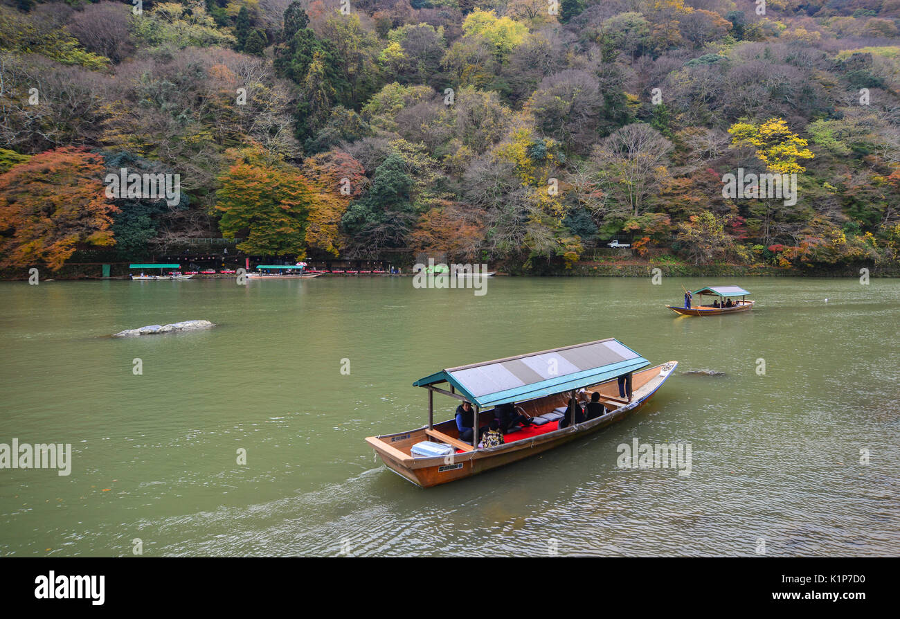 Kyoto, Japan - Nov 28, 2016. Boatman punting the boat for tourists to enjoy the autumn view along the bank of Hozu river in Arashiyama, Kyoto, Japan. - Stock Image