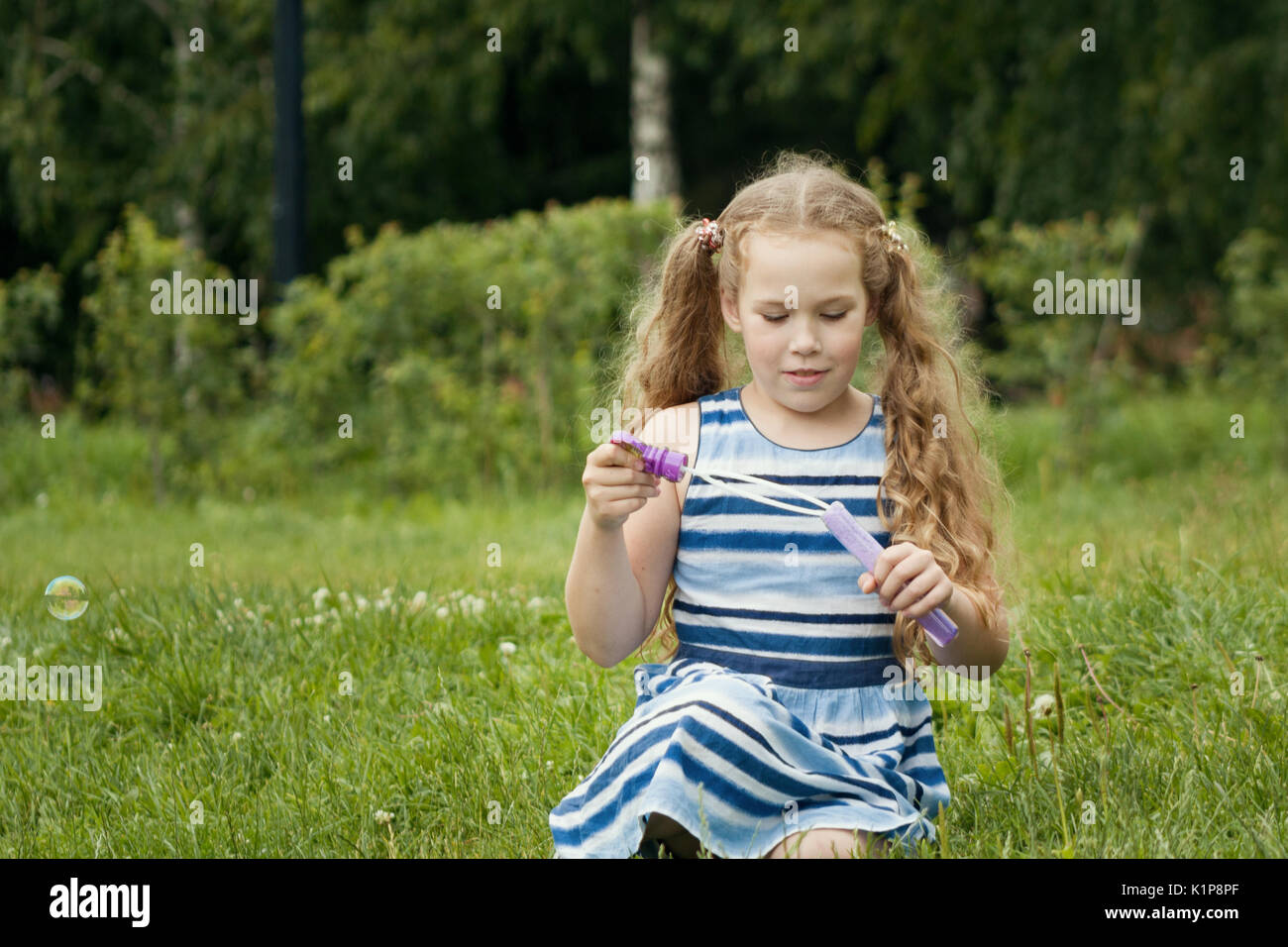 Little child girl playing with soap bubble in summer park - Stock Image