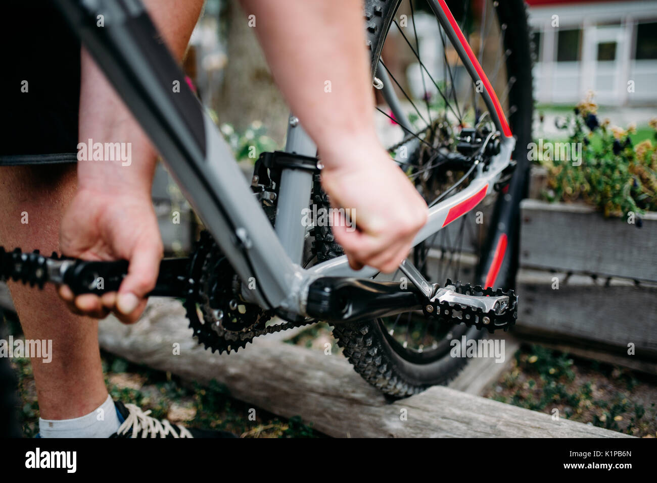 Bicycle mechanic hands adjusts with service tools cycling pedals. Cycle workshop outdoor. Bicycling sport, repairman - Stock Image