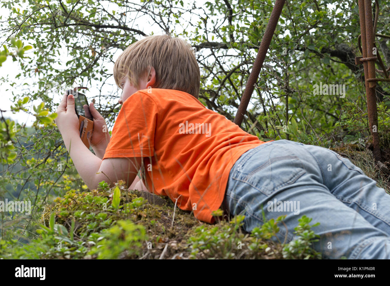 young boy lying on his belly taking pictures with his smartphone - Stock Image