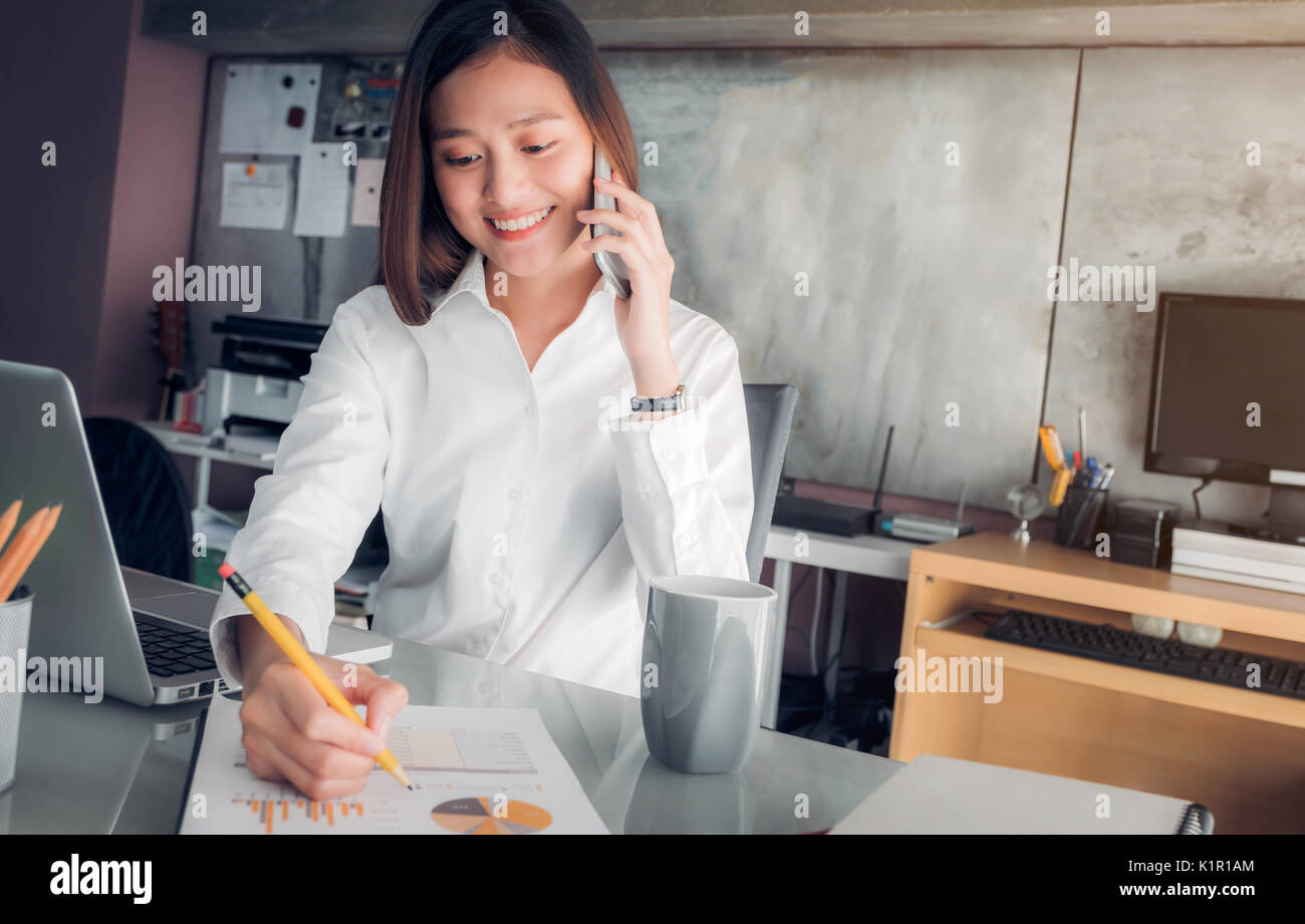 Asian businesswoman with smiling face talking on mobile and writing analyze business data on sheet on desk with colleague on phone ,Office life concep - Stock Image