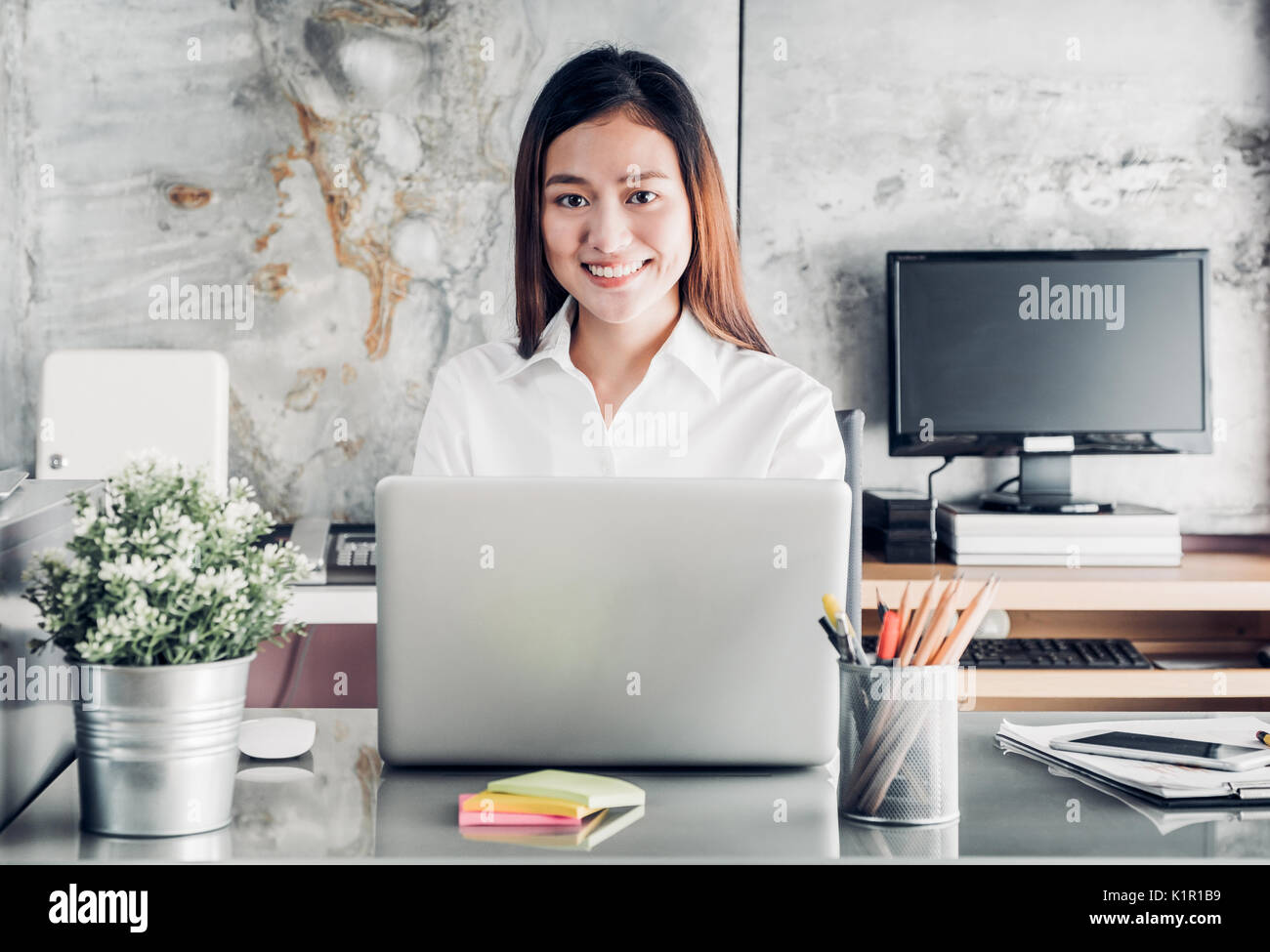 Asian businesswoman working with laptop computer on desk with smiling face,Happy office life concept,working woman at modern home office. - Stock Image