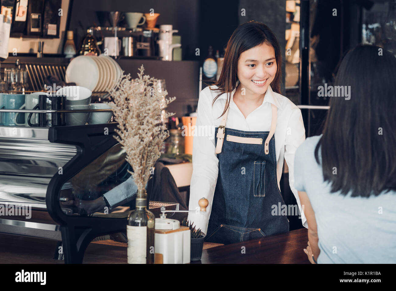 Asian woman barista wear jean apron holding coffee cup served to customer at bar counter with smile emotion,Cafe restaurant service concept,Owner smal - Stock Image