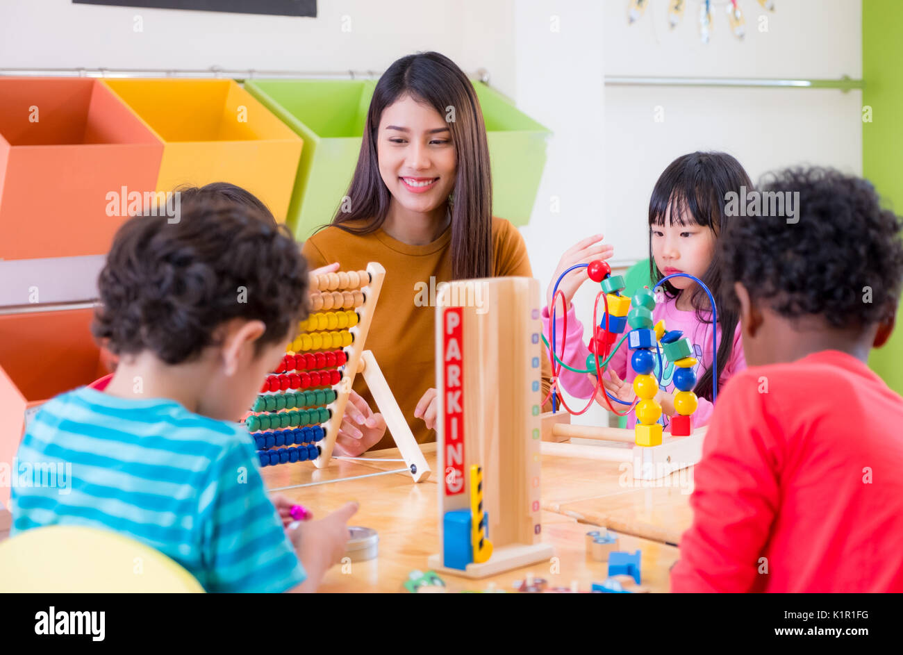 Asian female teacher teaching mixed race kids play toy in  classroom,Kindergarten pre school concept