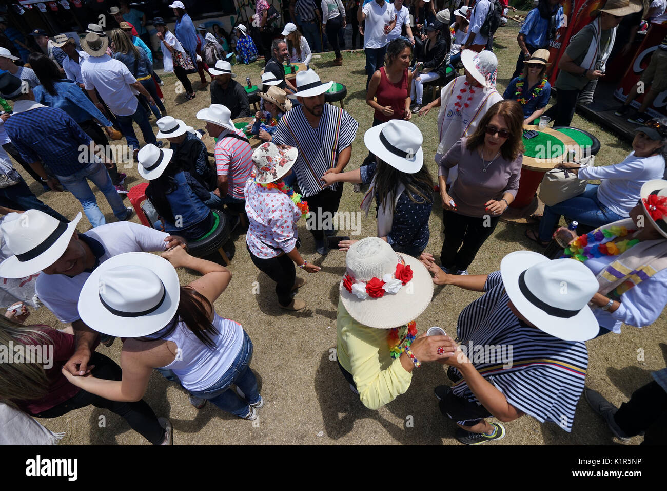 August 6, 2017 Medellin, Colombia: tourists wearing sombreros and ponchos dancing outdoors during the flower festival long weekend - Stock Image