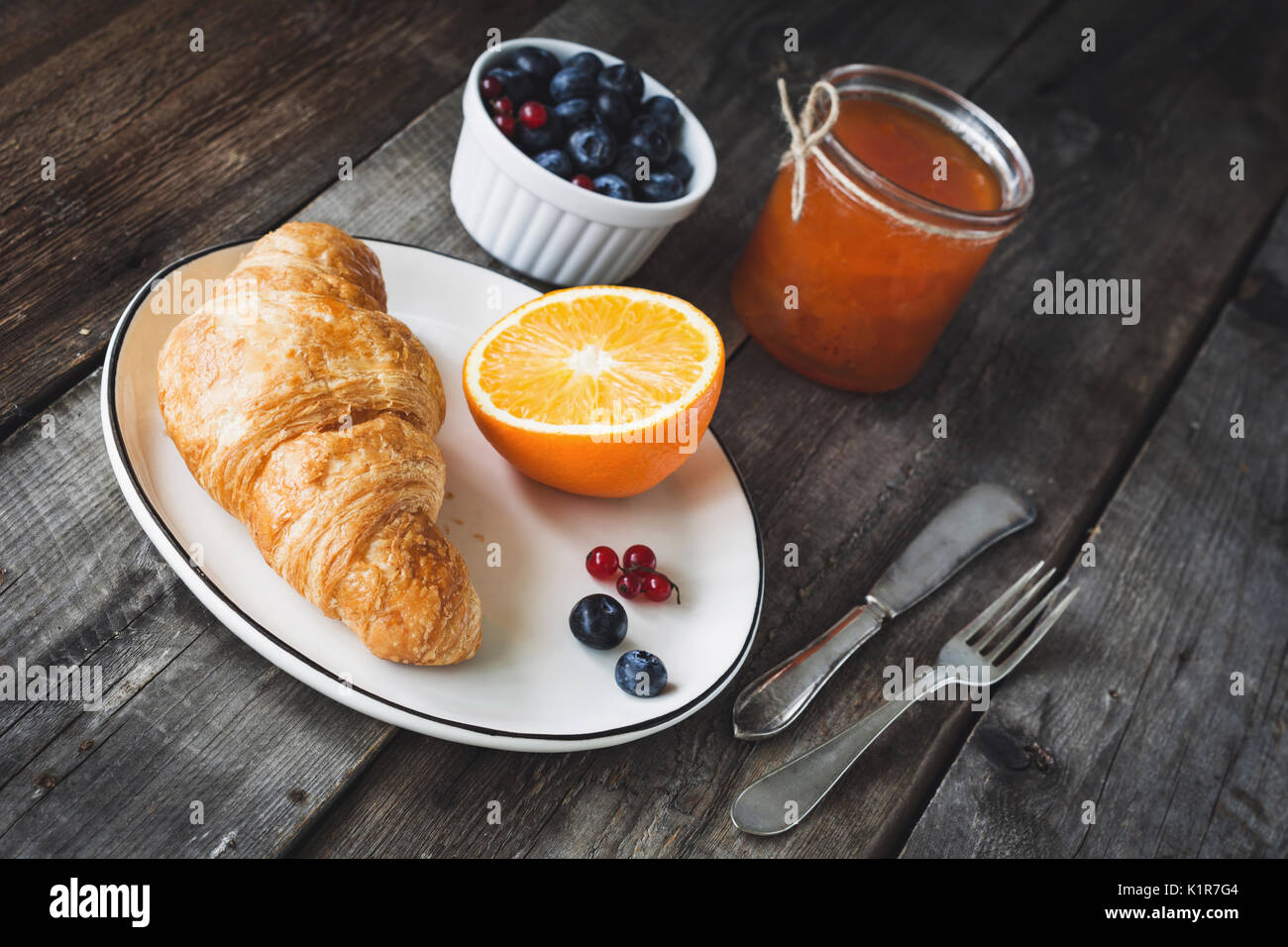 Fresh croissant, blueberries, orange and apricot jam on rustic wooden table. Angle view. Continental breakfast - Stock Image