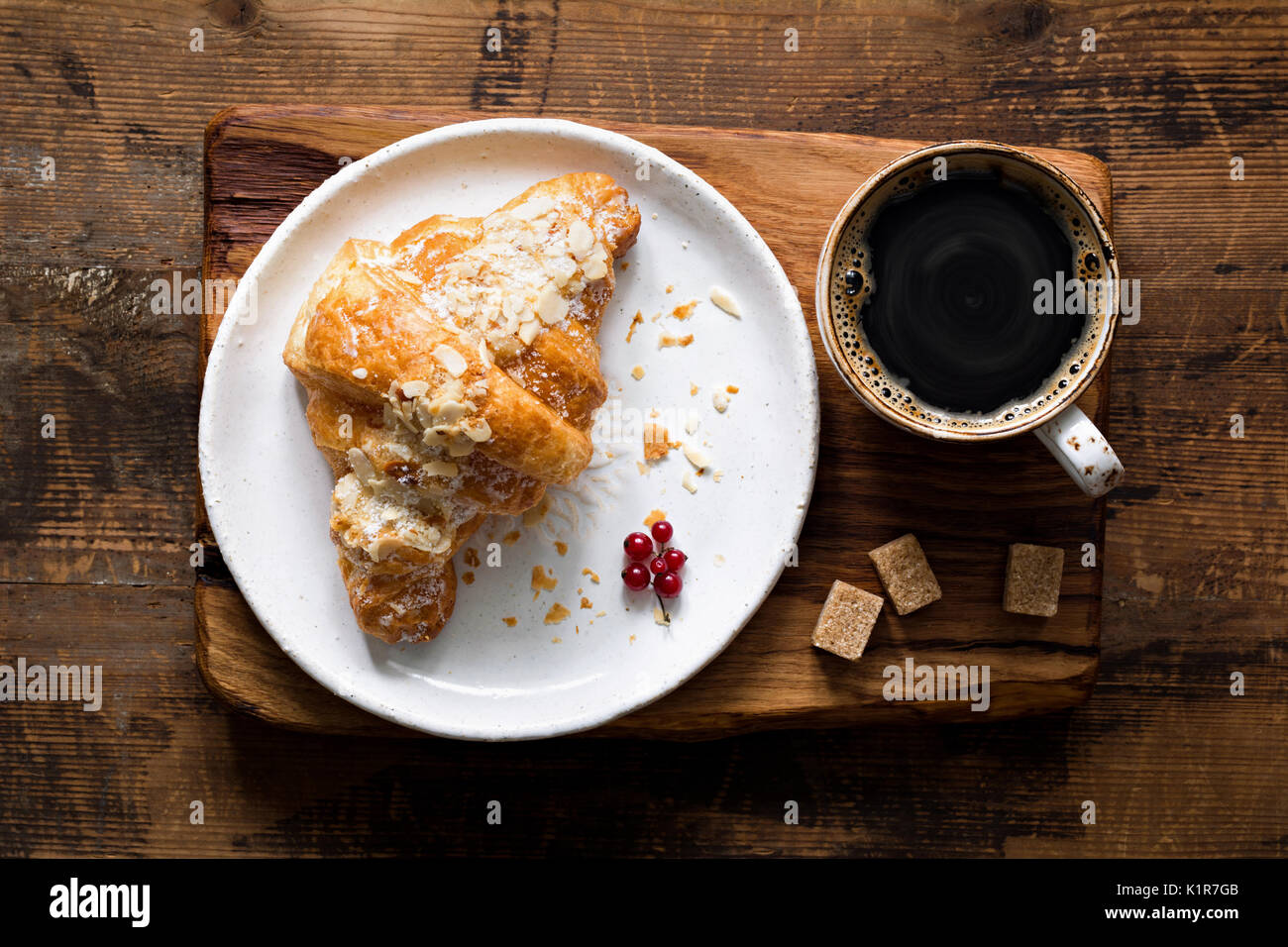 Almond croissant and cup of black coffee espresso on wooden cutting board. Table top view - Stock Image