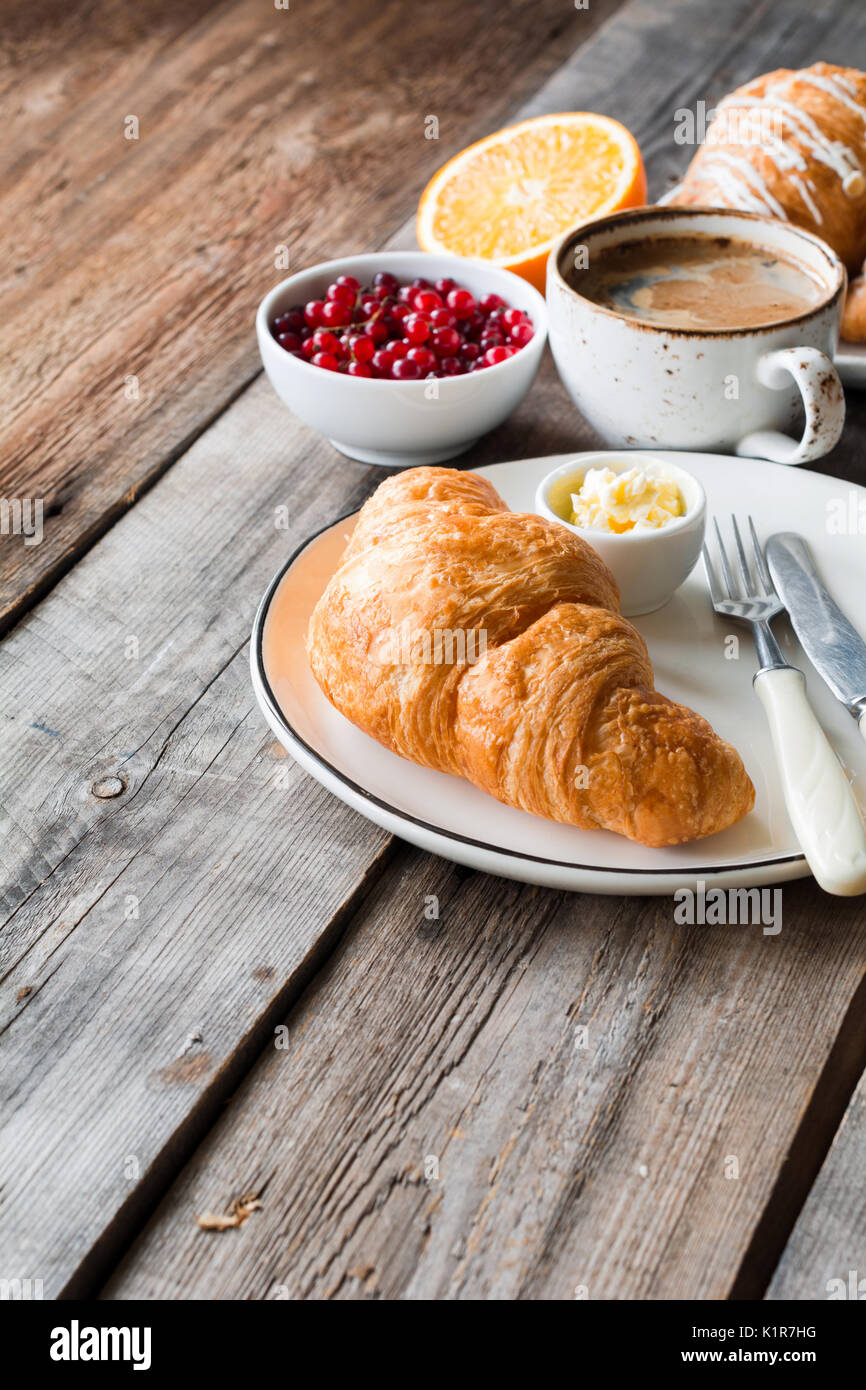 Fresh croissant, cup of coffee, orange, berries on rustic wooden table. Angle view and copy space. Continental breakfast - Stock Image