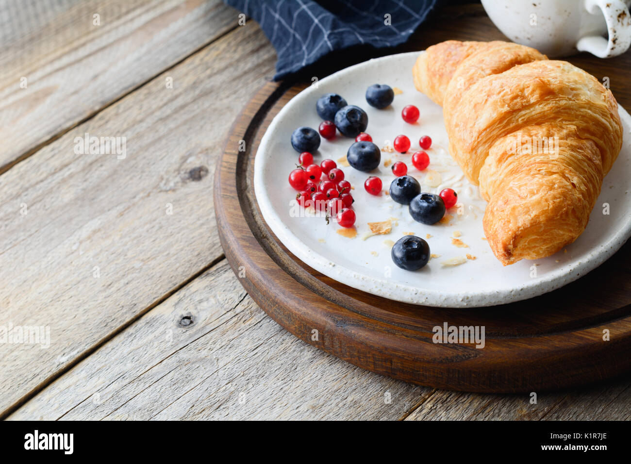 Fresh croissant, blueberries, red currants on white plate and cup of coffee on wooden tray. Continental breakfast - Stock Image