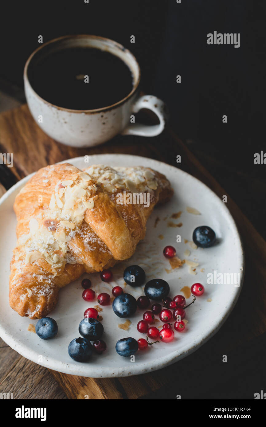 Almond croissant, berries and cup of coffee. Closeup view, toned image - Stock Image